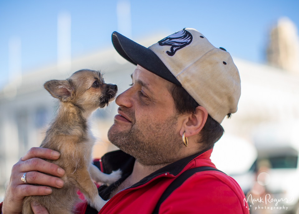 homeless man looks at small brown puppy