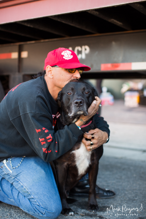 homeless man in red hat hugs large black dog