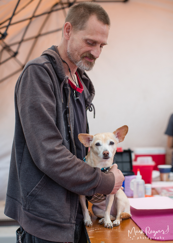 homeless man comforts his chihuahua during veterinary exam