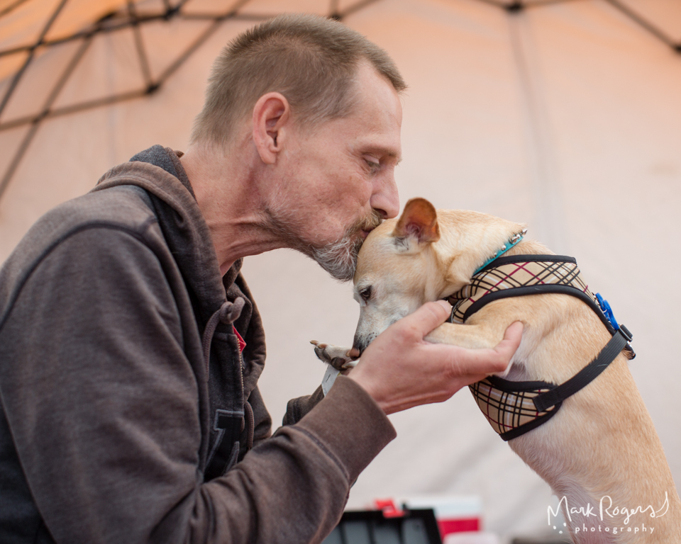 homeless man kisses his dog on the head