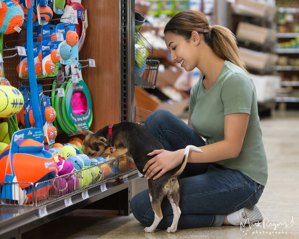 woman shopping for toys with puppy