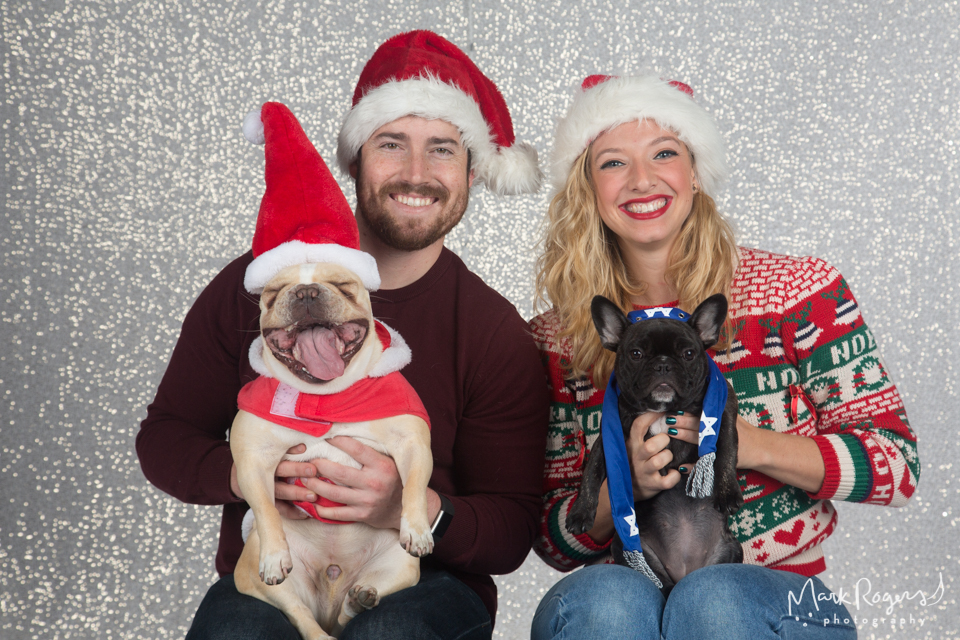 dog in santa suit yawning with family